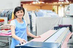 妇女洗衣店工作者轻拍在自动机器的亚麻布 免版税库存照片