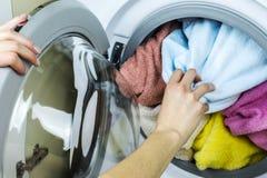 妇女从洗衣机得到衣裳 库存照片