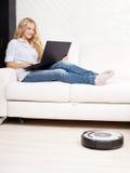 妇女说谎在沙发的和机器人吸尘器清洗 免版税库存照片