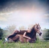妇女说谎并且拥抱在自然背景的一匹休息的马与天空 免版税库存图片