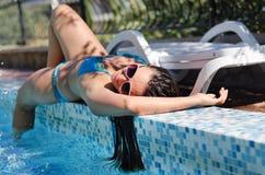 妇女说谎的晒日光浴在水池边缘 免版税图库摄影