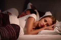 妇女说谎醒在遭受以失眠的床上 免版税库存图片