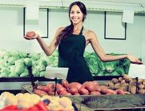 妇女画象卖有机土豆的围裙的在商店 免版税库存照片