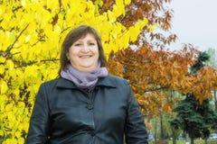 妇女画象反对秋天树背景的  图库摄影