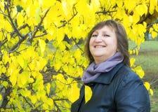 妇女画象反对秋天树背景的  免版税库存图片