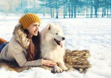 妇女画象和白色萨莫耶特人尾随说谎在雪 免版税库存图片