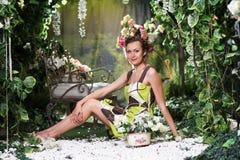 妇女画象在绿色花卉庭院里 免版税库存照片