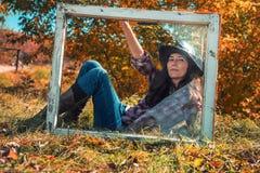 年轻妇女画象坐窗台 免版税库存图片