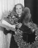 妇女画象有圣诞节花圈的和礼物(所有人被描述不更长生存,并且庄园不存在 供应商warr 库存照片