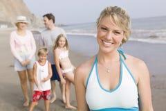 妇女画象海滩的与家庭 免版税库存图片