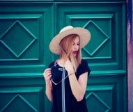 妇女画象的室外关闭时兴的黑礼服、太阳镜和黄色帽子的 背景秀丽城市生活方式都市妇女年轻人 图库摄影