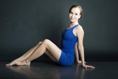 妇女画象蓝色短的礼服的坐在黑暗的背景的地板 免版税库存图片