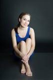 妇女画象蓝色短的礼服的坐在黑暗的背景的地板 库存照片