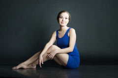 妇女画象蓝色短的礼服的坐在黑暗的背景的地板 免版税库存照片