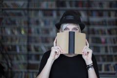 妇女画象黑帽会议的有被打开的书的,面对半隐蔽,白发 行家学生女孩在图书馆里 免版税库存照片