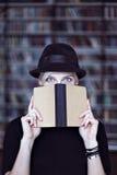 妇女画象黑帽会议的有被打开的书的,面对半隐蔽,白发 行家学生女孩在图书馆里 免版税库存图片