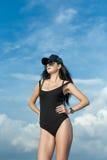 妇女画象黑紧身衣裤、棒球帽和太阳镜的 免版税库存图片