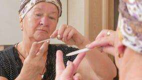 妇女年迈做在浴的修指甲  它使用一把指甲锉 在镜子箱子能被看见反射了 beauvoir 股票录像