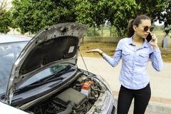 妇女紧随一辆残破的汽车,她在电话的` s需要帮助,因为汽车不刺激 免版税库存图片