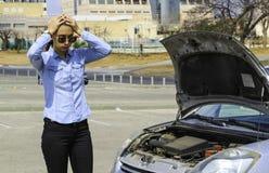 妇女紧随一辆残破的汽车,需要帮助,并且她拿着她的头,因为汽车不刺激 免版税库存图片