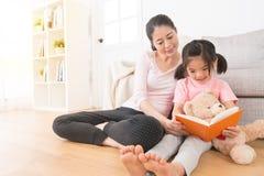妇女伴随读故事书的孩子 库存照片