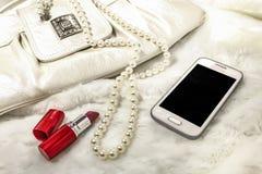 妇女` s传动器,唇膏,项链,在白色毛皮的电话 库存图片