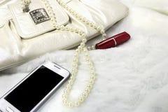 妇女` s传动器,唇膏,项链,在白色毛皮的电话 免版税库存照片