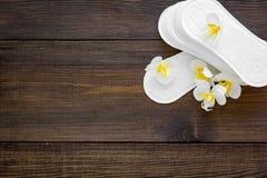 妇女` s卫生学方面的产品 重要几天概念 在小花附近的月经带在黑暗的木背景顶视图 免版税图库摄影