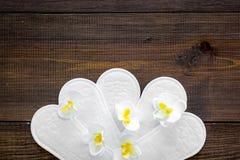 妇女` s卫生学方面的产品 重要几天概念 在小花附近的月经带在黑暗的木背景顶视图 免版税库存照片