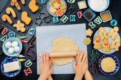 妇女` s和儿童` s手铺开与ingredie的姜面团 库存图片