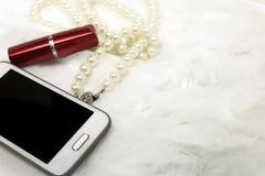妇女` s唇膏,项链,在白色毛皮的电话 库存照片