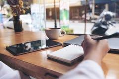 妇女` s在一个空白的笔记本的手文字的特写镜头图象有膝上型计算机、片剂和咖啡杯的在木桌上 库存图片