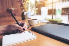 妇女` s在一个空白的笔记本的手文字的特写镜头图象有膝上型计算机、片剂和咖啡杯的在木桌上 免版税图库摄影