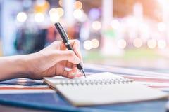妇女` s在一个笔记本的手文字有在一张木书桌上的一支笔的 图库摄影