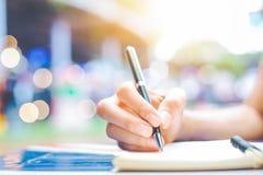 妇女` s在一个笔记薄的手文字与在一张木书桌上的一支笔 免版税库存照片