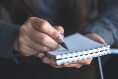 妇女` s在办公室递举行和写在桌上的一个空白的白色笔记本 图库摄影