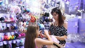 妇女` s在商城的头发辅助部件 女孩、孩子和妈咪在商店选择簪子,橡皮筋儿,发带, 股票录像
