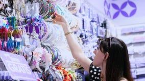 妇女` s在商城的头发辅助部件 女孩,妇女在商店选择簪子,橡皮筋儿,发带, 影视素材