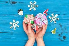 妇女` s在木雪花和新年装饰品附近递拿着圣诞节礼物盒在蓝色老桌上 图库摄影