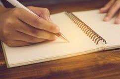 妇女` s在纸的手文字特写镜头  库存照片