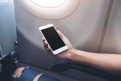 妇女` s在飞机窗口旁边递拿着有空白的黑桌面屏幕的一个白色巧妙的电话 库存图片