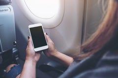 妇女` s在飞机窗口旁边递拿着有空白的黑桌面屏幕的一个白色巧妙的电话 免版税库存图片