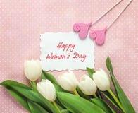 妇女` s天与白色郁金香和心脏的问候消息在别针 免版税库存图片