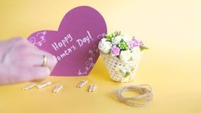妇女` s天概念 与花的篮子和与愉快的妇女` s天题字的纸心脏在金黄背景- 影视素材