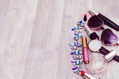 妇女` s套在木背景的时装配件:鞋子、提包和化妆用品 免版税图库摄影