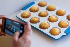 妇女` s手为在一个手机的煮熟的杯形蛋糕照相 面包店设计图象产品 图库摄影