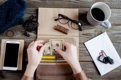 妇女` s手使金钱脱离在工作区的钱包 免版税库存图片