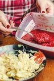 妇女` s手倾倒在一个被磨碎的苹果之上的山莓果酱在板材 免版税库存图片