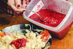 妇女` s手倾倒在一个被磨碎的苹果之上的山莓果酱在板材 免版税库存照片