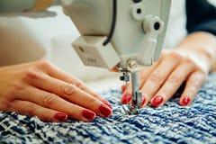 妇女` s手在与缝纫机一起使用 库存图片